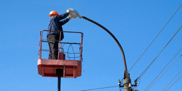 electrician climb work installing new street lamp on electricity power concrete pole in blue sky